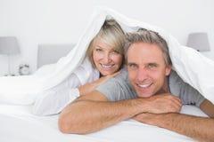 微笑在盖子下的愉快的夫妇对照相机 免版税库存照片