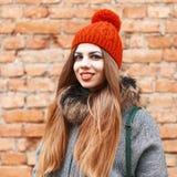 微笑在砖红色墙壁附近的美丽的女孩在冬日 免版税库存照片