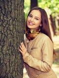 微笑在秋天公园的女孩 免版税库存照片