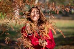 微笑在秋天树后的美丽的年轻女人 免版税库存照片