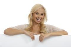 微笑在空白页之后的美丽的妇女 免版税库存图片