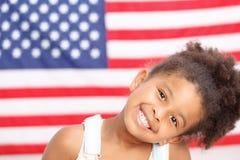 微笑在美国旗子前面的逗人喜爱的学龄前女孩 免版税库存图片