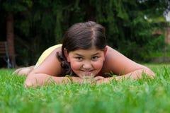 微笑在草放置的女孩吉普赛孩子 免版税图库摄影