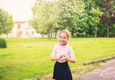 微笑在草甸的愉快的青春期前的女孩在夏日对日落 库存图片