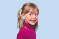 微笑在蓝色背景的美丽的女孩孩子 库存图片
