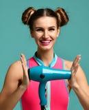 微笑在蓝色薄荷的背景的愉快的年轻深色的妇女举行绿色吹风器 库存照片