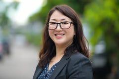 微笑在街道的成熟愉快的美丽的亚裔女实业家户外 免版税库存照片