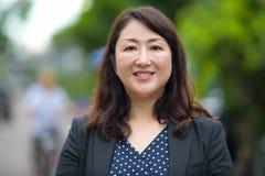 微笑在街道的成熟愉快的美丽的亚裔女实业家户外 库存照片