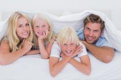 微笑在被子下的家庭的画象 库存照片
