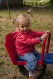 微笑在跷跷板的小女孩 库存照片