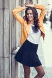 微笑在都市背景中的年轻深色的妇女 免版税库存照片