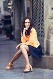 微笑在都市背景中的年轻深色的妇女 库存照片