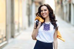 微笑在都市背景中的年轻深色的妇女 免版税库存图片
