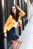 微笑在都市背景中的年轻深色的妇女 库存图片