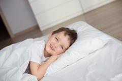 微笑在醒的小男孩在白色床上期间 免版税库存图片