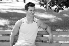 微笑在长木凳的运动员在公园 免版税库存照片