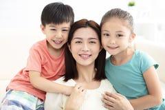 微笑在长沙发的母亲和孩子 免版税库存图片