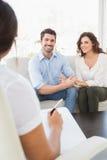 微笑在长沙发的被和解的夫妇 免版税库存照片