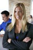 微笑在队前面的白肤金发的女性女商人在砖都市办公室 库存照片