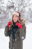 微笑在雪的女孩戴伐木工人帽子 库存照片