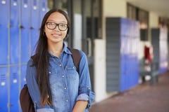 微笑在高中走廊的愉快的亚裔十几岁的女孩 免版税库存图片