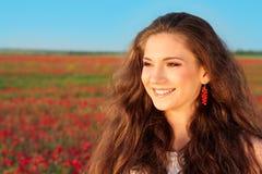 微笑在鸦片领域的日落的少妇 免版税库存照片