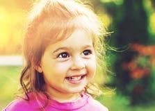 微笑在晴朗的夏日的逗人喜爱的小女孩被定调子的画象  免版税库存照片