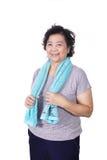 微笑在锻炼以后的老亚裔妇女,拿着毛巾在脖子上 库存照片