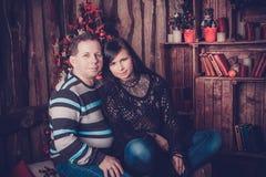 微笑在他们的圣诞树旁边的爱恋的夫妇 免版税库存照片