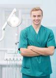 微笑在他的牙齿办公室的年轻牙医 免版税图库摄影