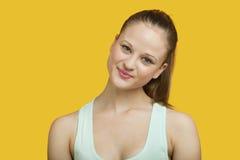 微笑在黄色背景的美丽的少妇画象  免版税图库摄影