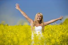 微笑在黄色花的领域的一个美丽的女孩 免版税库存图片