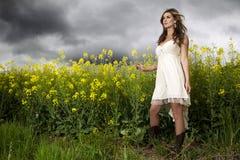 微笑在黄色花的领域的一个美丽的女孩 免版税库存照片