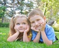 微笑在绿草的愉快的孩子 免版税库存图片