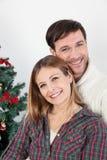 微笑在chrismas树旁边的夫妇 免版税库存照片