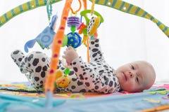 微笑在playmat的愉快的男婴 库存图片