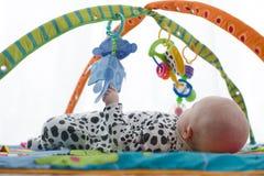 微笑在playmat的愉快的男婴 库存照片