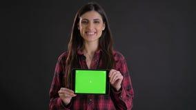 微笑地显示水平的片剂的绿色屏幕在黑背景的年轻白种人长发女孩画象  股票视频