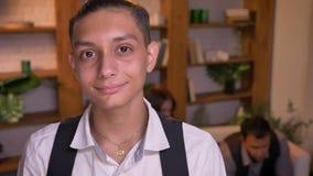 微笑地观看直接地入与他的家庭的照相机的少年阿拉伯男孩特写镜头画象在背景 股票录像