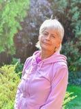 微笑外面在晴天期间的老妇人 免版税库存照片