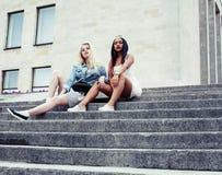微笑大学大厦两个十几岁的女孩的infront,有 免版税库存照片