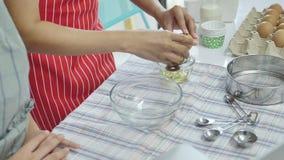 微笑女儿的接近的手,笑,当烤蛋到碗一起时 影视素材