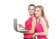 微笑女孩的膝上型计算机二个年轻人 免版税库存照片