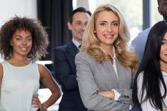 微笑女实业家领导买卖人的小组在现代办公室,在商人被折叠的队立场的女性上司 免版税库存照片