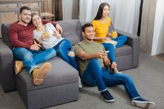 微笑好奇的朋友,当观看电视时的一个有趣的节目 库存图片