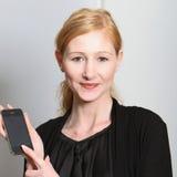 微笑存在的smartphone他们的妇女年轻人 免版税库存图片