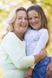 微笑孙女的祖母户外 免版税图库摄影