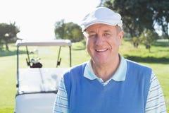 微笑对与后边高尔夫球儿童车的照相机的愉快的高尔夫球运动员 库存照片