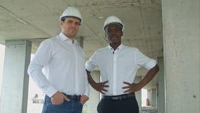 微笑对与安全帽的照相机的建筑队 免版税库存图片