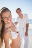 微笑对与握她的手的男朋友的照相机的白肤金发的妇女 免版税库存图片